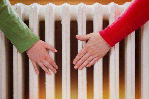 Manos en el radiador de una casa